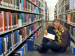 student sitting in the aisle of library